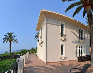 krēma krāsas māja ar palmu un dārzu
