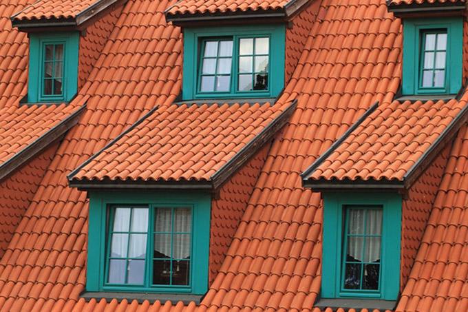 oranžs mājas jumts ar zilzaļiem logiem