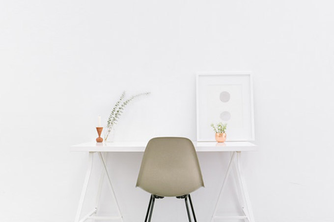 krēsls, balta siena un balts galds ar augiem